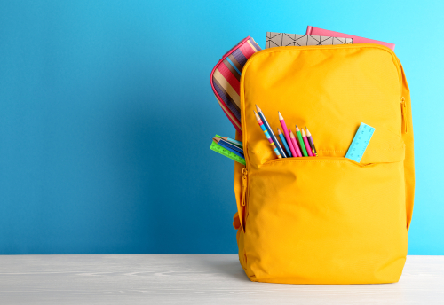 Yellow backpack with pencils sticking out of it