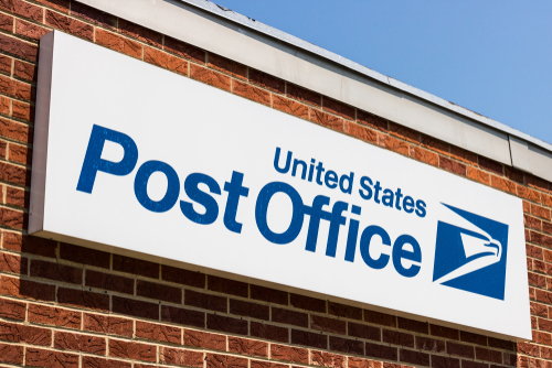 post office sign on a brick building