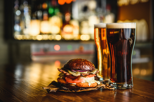 Cheeseburger and two beers in a dimly lit bar